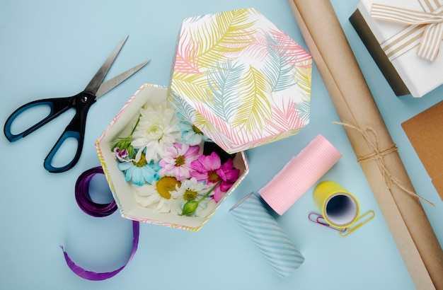 데이지와 화려한 국화 꽃으로 가득 선물 상자의 상위 뷰 파란색 배경에 종이와 종이 클립의 롤