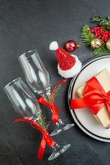 Вид сверху подарочной коробки на обеденной тарелке рождественская елка еловые ветки хвойная шишка шляпа санта-клауса упавшие стеклянные кубки на темном фоне