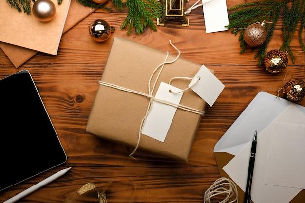 Вид сверху подарочной коробки планшета поздравительной открытки и украшений в рождественской концепции на деревенском столе