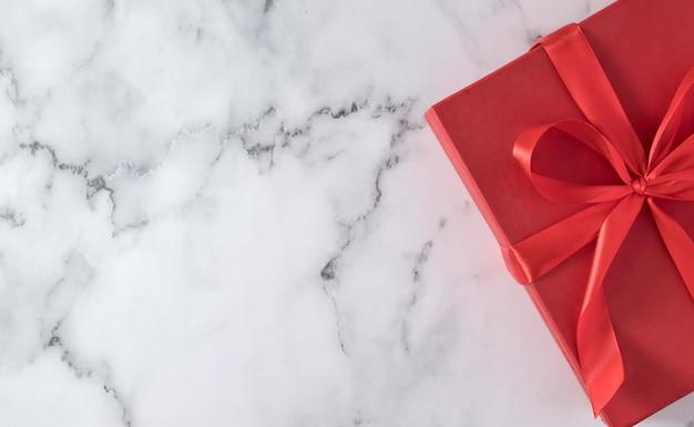 コピースペースの大理石のテーブルに弓とギフトボックスの上面図