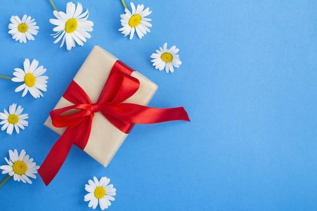 Вид сверху подарочной коробки с красной лентой и белыми ромашками на синей поверхности