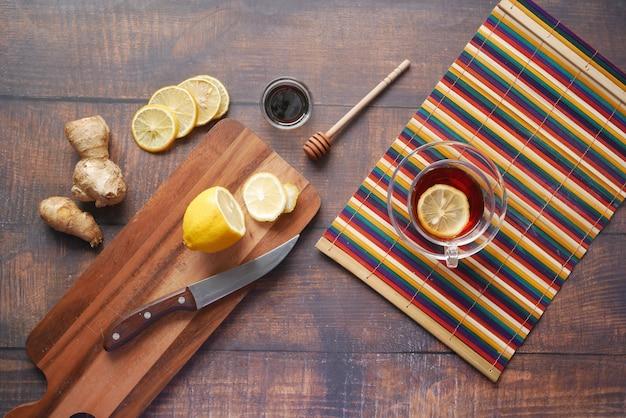 Вид сверху имбиря и чая с лимоном на деревянных фоне