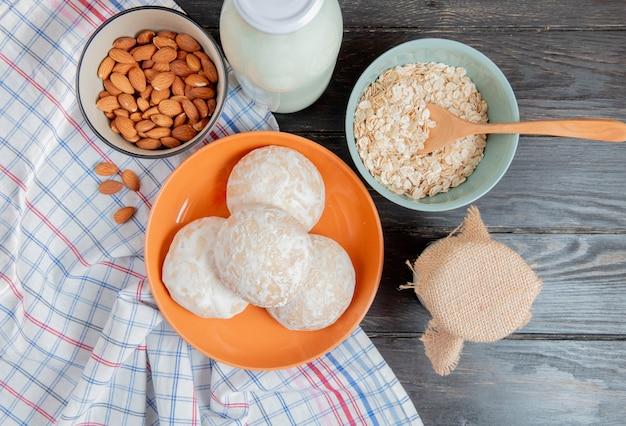 格子縞の布のアーモンドとプレートのジンジャーブレッドの平面図と木製のテーブルのスプーンでサワークロテッドミルククリームオート麦フレーク