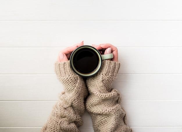 Вид сверху девушки в свитере, держащей кофейную кружку на белом столе