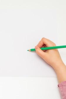 녹색 연필로 흰색 빈 종이에 그리는 소녀의 손의 상위 뷰. 모형. 텍스트를 위한 빈 공간입니다.