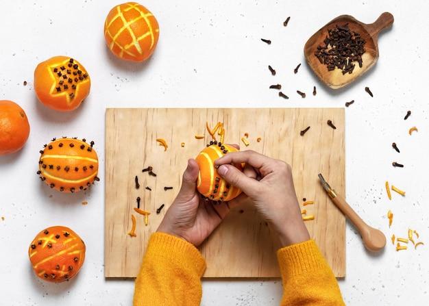 오렌지, 상위 뷰에 정향 장식품을 만드는 여자의 손의 상위 뷰