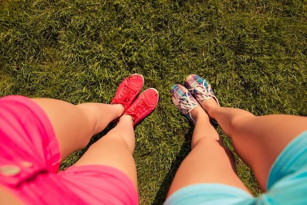 Вид сверху на ноги девушки и две пары кроссовок, идущих по зеленой лужайке
