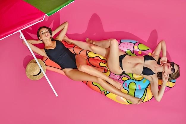 Вид сверху девушек в купальниках, лежащих на надувном матрасе под зонтиком от солнца на розовой поверхности