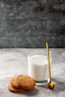 空き領域のある暗い背景の灰色のテーブルにミルクと金のスプーンのクッキーで満たされたガラスカップの上面図