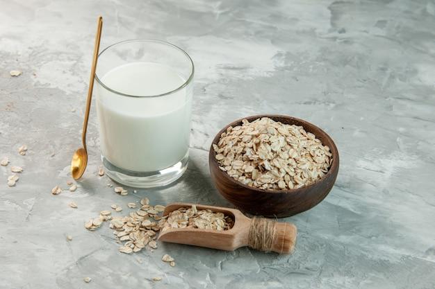 회색 배경에 있는 갈색 냄비 내부와 외부에 우유와 귀리로 채워진 유리 컵의 상단