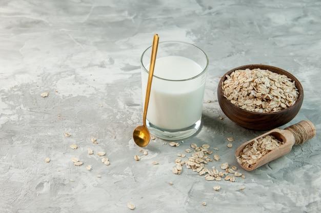회색 배경의 왼쪽에 있는 갈색 냄비 내부와 외부에 우유와 귀리로 채워진 유리 컵의 상단