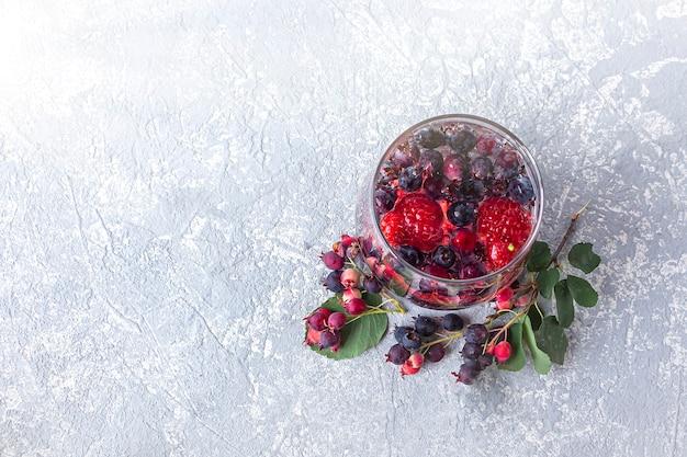 Вид сверху стакана детокс-напитка с ягодами и лимоном на бетонном фоне