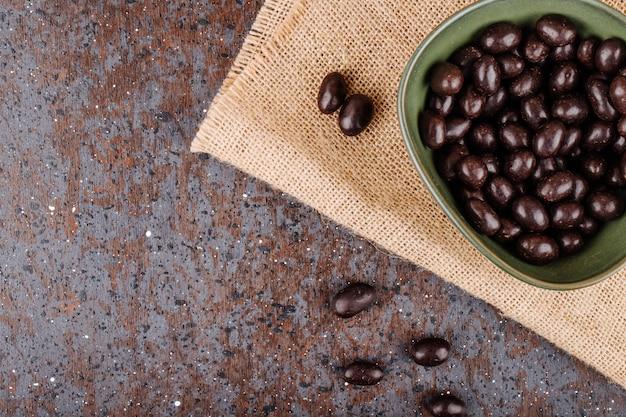 Вид сверху глазированные шоколадные ореховые конфеты в миску на вретище на деревенском фоне с копией пространства