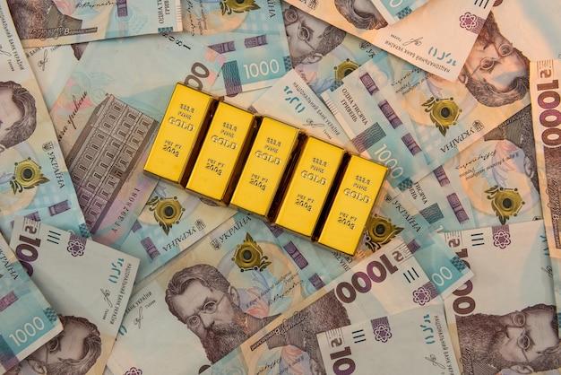 Вид сверху золотых слитков, лежащих на фоне украинских денег