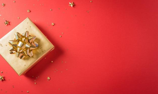 복사 공간이 있는 빨간색 배경에 리본이 있는 황금 크리스마스 선물 상자의 상위 뷰