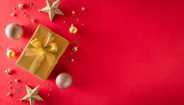 Вид сверху на золотую подарочную коробку с елочным шаром и звездой