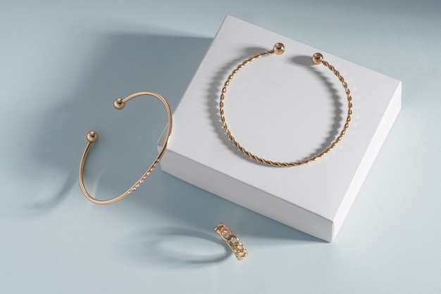 コピースペースと青い紙の背景の上の白いボックスに金色のジュエリーブレスレットとリングの上面図
