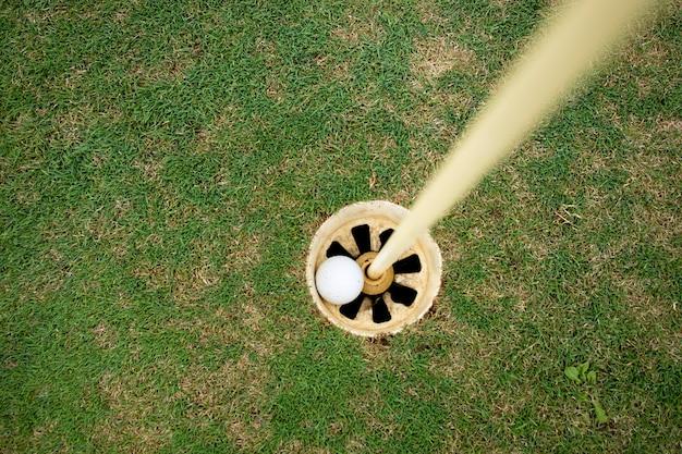 Вид сверху мяч для гольфа в лунке.
