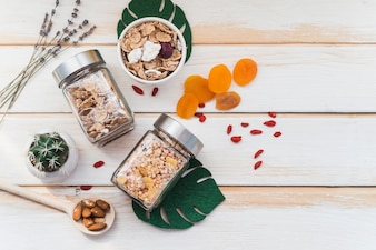 Top view of granola and cornflake jar near dry fruits and succulent plant on wooden background