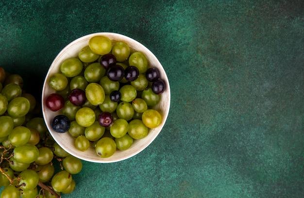 コピースペースと緑の背景にボウルとブドウの房のブドウの果実の上面図