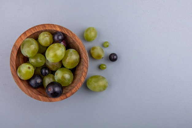 ボウルとコピースペースと灰色の背景にブドウの果実の上面図
