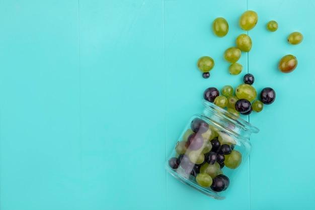 Вид сверху на виноградные ягоды, разливающиеся из стеклянной банки на синем фоне с копией пространства