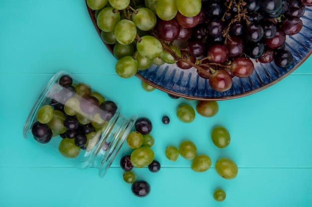 Вид сверху на виноградные ягоды, разливающиеся из стеклянной банки с виноградом в тарелке на синем фоне