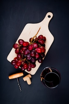 ガラスの赤ワインとまな板の上のブドウと黒いテーブルの上のコルク抜きとコルク