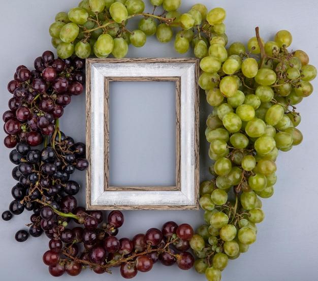 Вид сверху винограда вокруг рамки на сером фоне с копией пространства