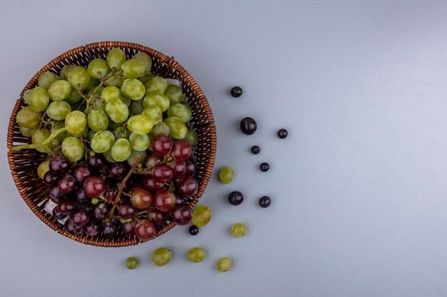 Вид сверху на виноград в корзине и узор из виноградных ягод на сером фоне с копией пространства