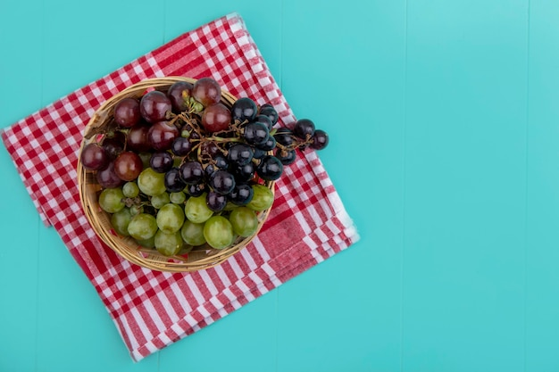 コピースペースと青色の背景に格子縞の布の上のバスケットにブドウのトップビュー