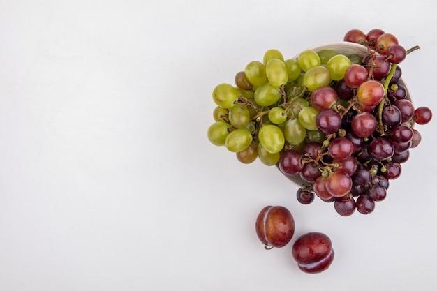 コピースペースと白い背景の上のボウルにブドウのトップビュー