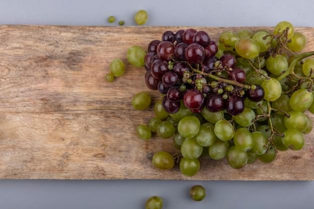 Вид сверху винограда на разделочной доске на сером фоне с копией пространства