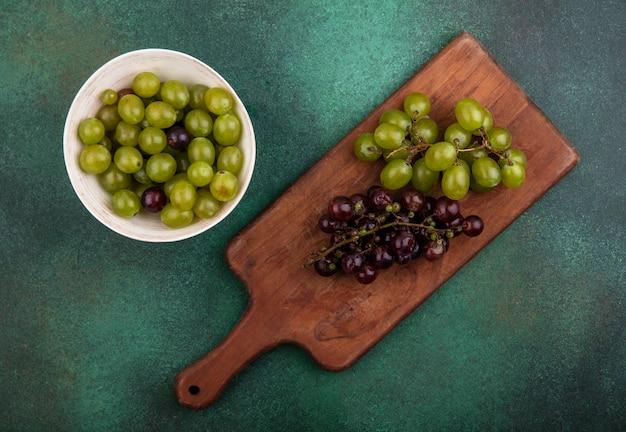 緑の背景にボウルにブドウの果実とまな板の上のブドウのトップビュー