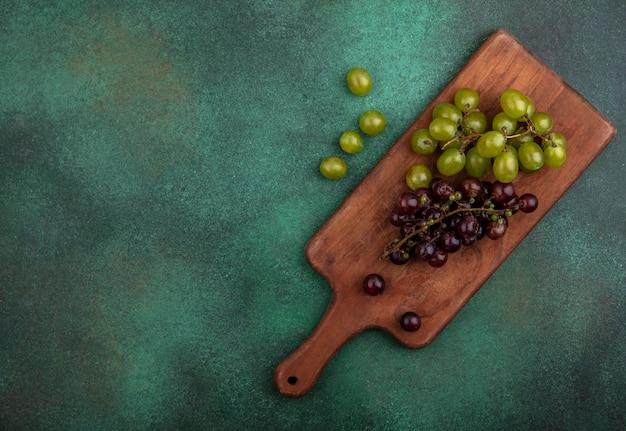 コピースペースと緑の背景にブドウの果実とまな板の上のブドウのトップビュー