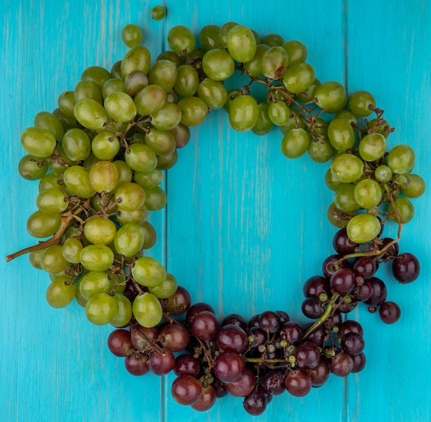 Вид сверху на виноград в круглой форме на синем фоне с копией пространства