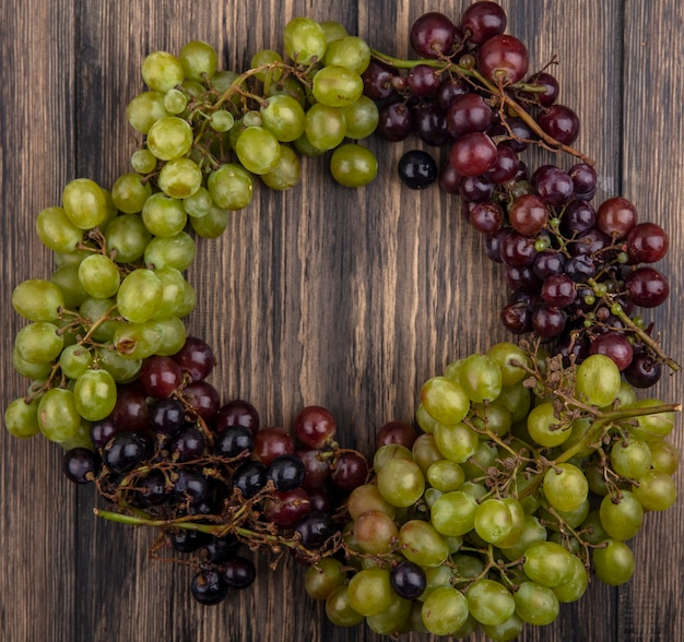 Вид сверху на виноград в круглой форме на деревянном фоне
