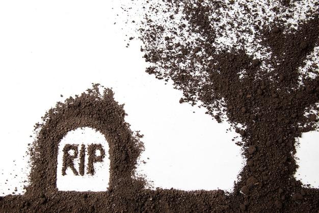 白い壁に裂け目の碑文と土が付いた墓の形の平面図