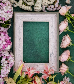 Вид сверху серой рамки со светло-розовыми цветами на зеленой поверхности