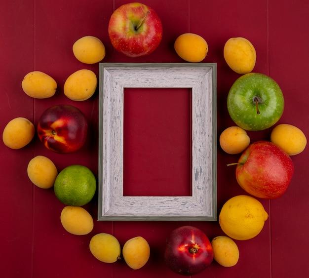 Вид сверху серой рамки с персиками, абрикосами и яблоками на красной поверхности