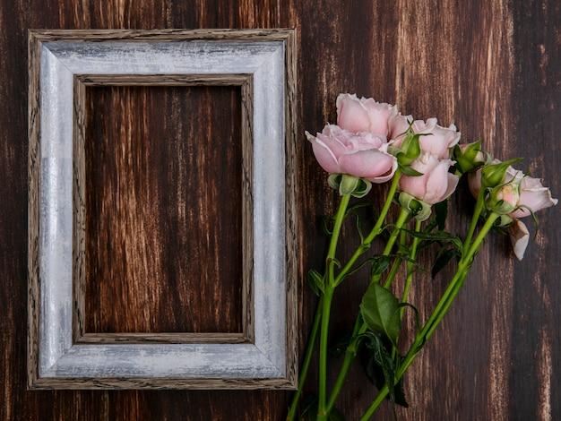 木製の表面にピンクのバラと灰色のフレームのトップビュー