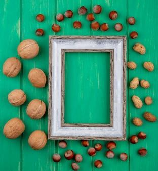 Вид сверху серой рамки с грецкими орехами, фундуками и арахисом на зеленой поверхности