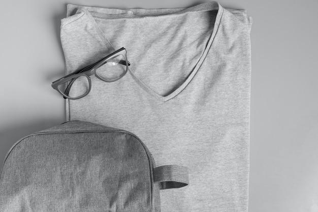 Вид сверху серой мужской модной футболки с серыми очками и серой сумкой для туалетных принадлежностей на сером