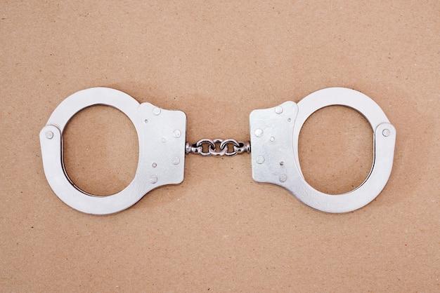 Вид сверху серых металлических наручников на коричневом фоне.