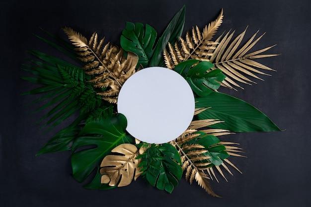 Вид сверху зеленых и золотых тропических листьев на старом черном деревянном полу