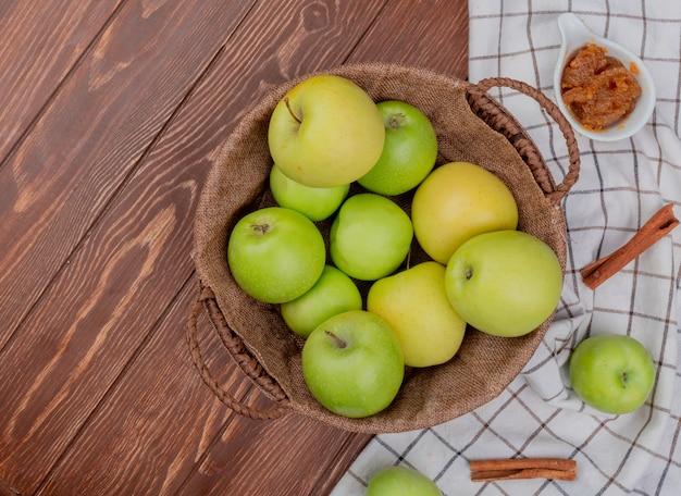 格子縞の布とコピースペース付きの木製テーブルにリンゴのジャムとシナモンが付いているバスケットの緑と黄色のリンゴのトップビュー