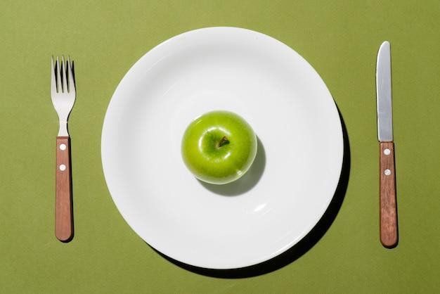 Вид сверху зеленого яблока на белой тарелке с ножом и вилкой на зеленом фоне