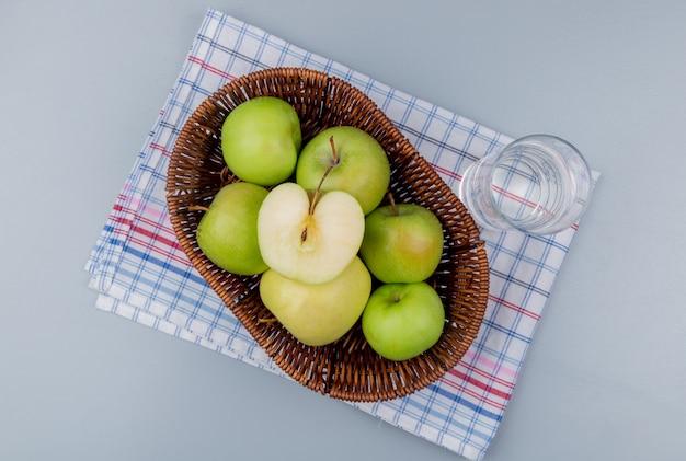 格子縞の布と灰色の背景にバスケットと水のガラスの青リンゴのトップビュー