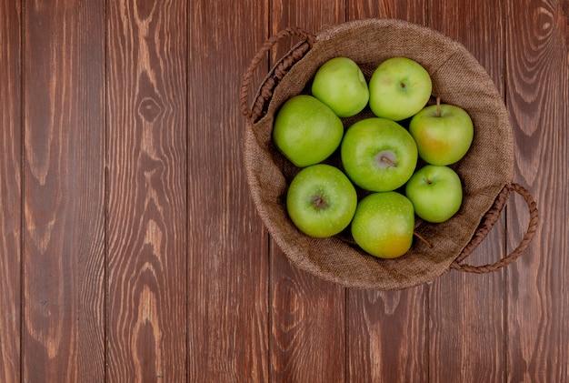 Вид сверху зеленых яблок в корзине на деревянном фоне с копией пространства