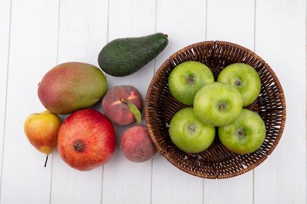 Вид сверху зеленых яблок на ведре с гранатом, манго, грушей, персиком, изолированным на белой поверхности